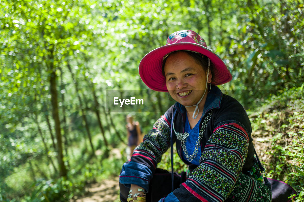 one person, tree, smiling, plant, real people, land, leisure activity, day, lifestyles, portrait, looking at camera, casual clothing, hat, clothing, forest, happiness, front view, focus on foreground, nature, outdoors, woodland