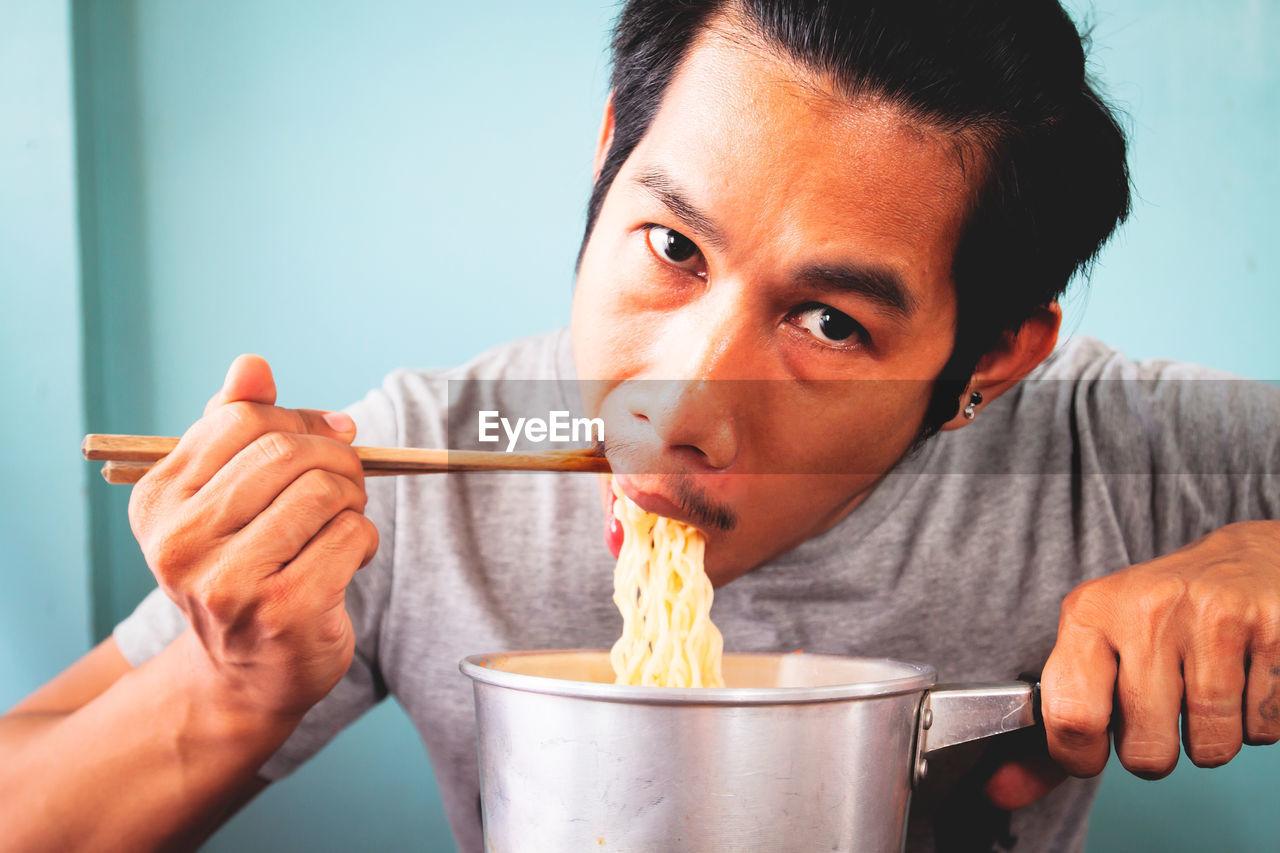 Portrait of man eating noodles at home