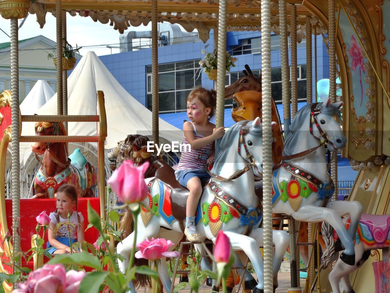 amusement park, childhood, carousel, enjoyment, amusement park ride, leisure activity, arts culture and entertainment, carousel horses, fun, girls, elementary age, outdoors, full length, merry-go-round, happiness, day, lifestyles, boys, real people, smiling, people