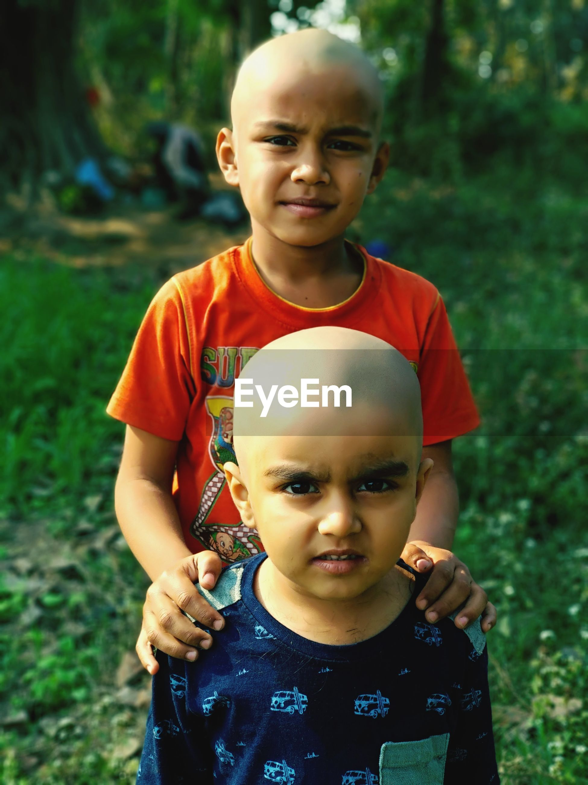 Portrait of cute brothers with shaved head standing on field
