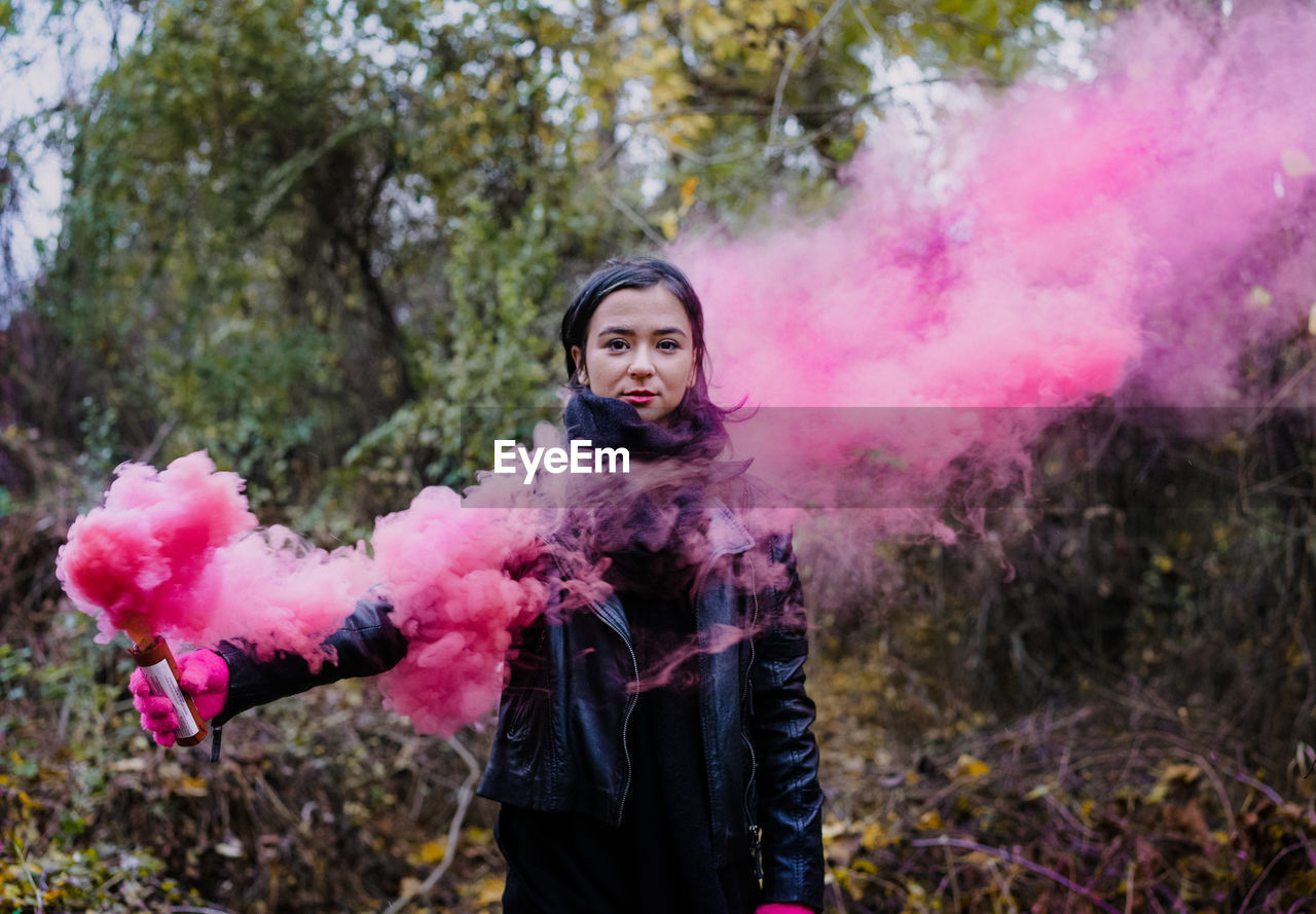 Portrait Of Young Woman Holding Distress Flare While Standing In Forest