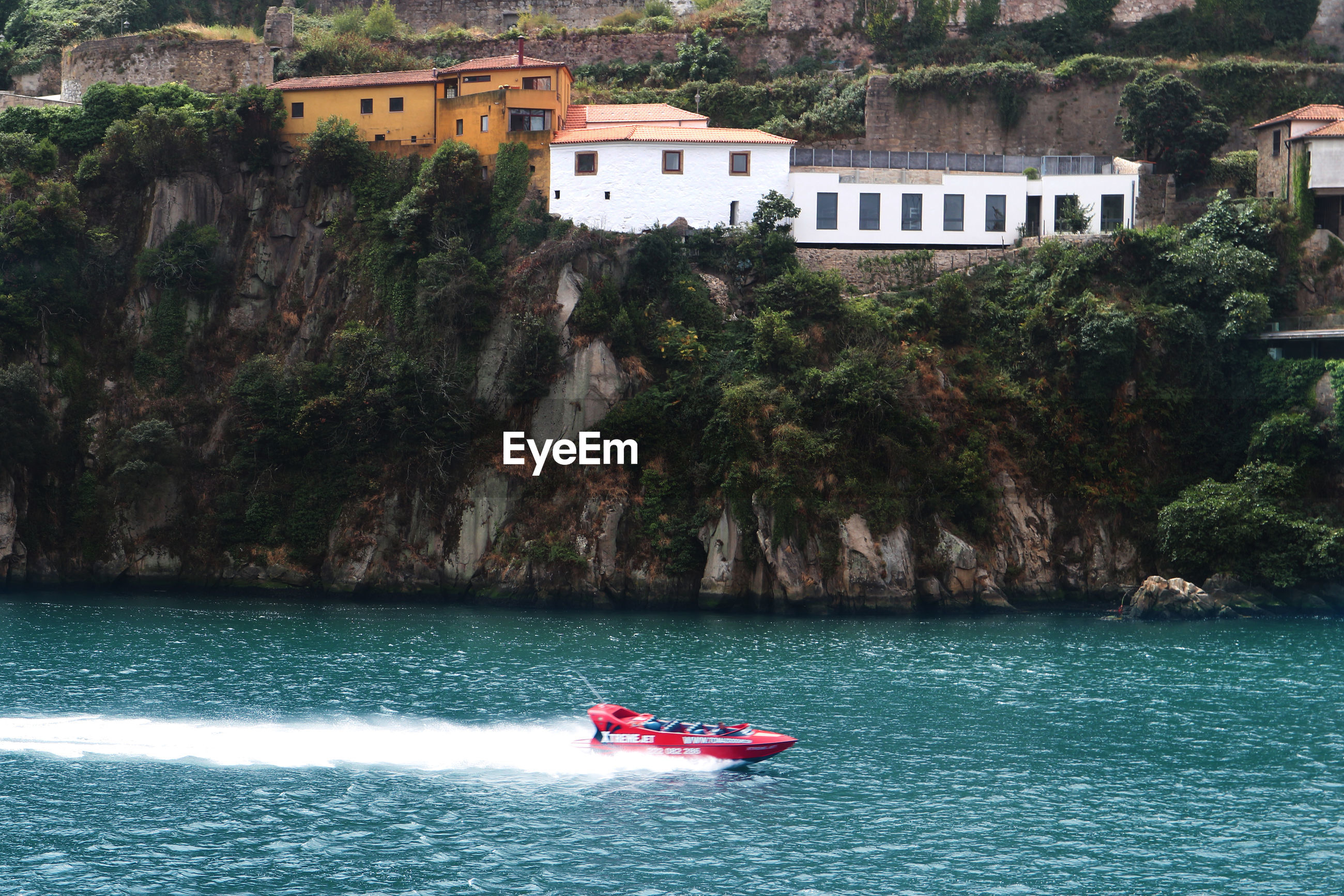 nautical vessel, transportation, water, boat, tree, day, mode of transport, nature, river, real people, waterfront, building exterior, outdoors, men, architecture, inflatable raft, cliff, built structure, beauty in nature, sailing, scenics, jet boat, people