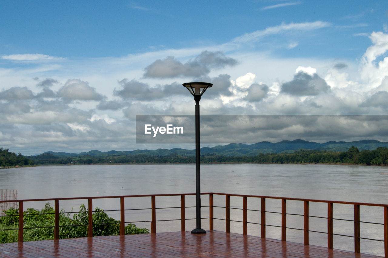 Street Light At Observation Point By River Against Cloudy Sky