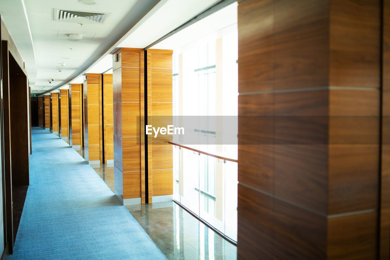 arcade, architecture, indoors, corridor, building, built structure, no people, door, entrance, flooring, empty, illuminated, wall - building feature, ceiling, the way forward, glass - material, direction, in a row, lighting equipment, day, modern, architectural column