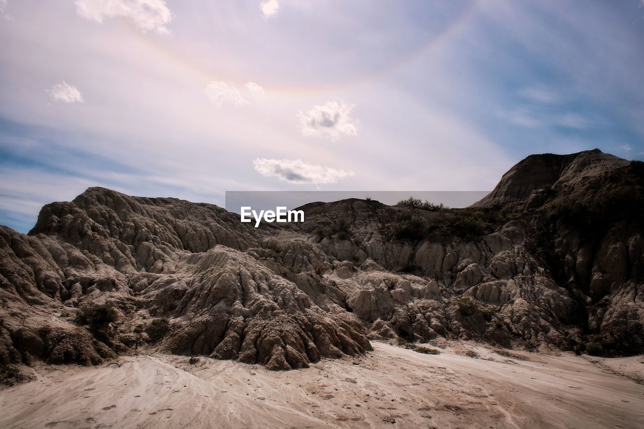 Scenic view of badland rock formations against sky