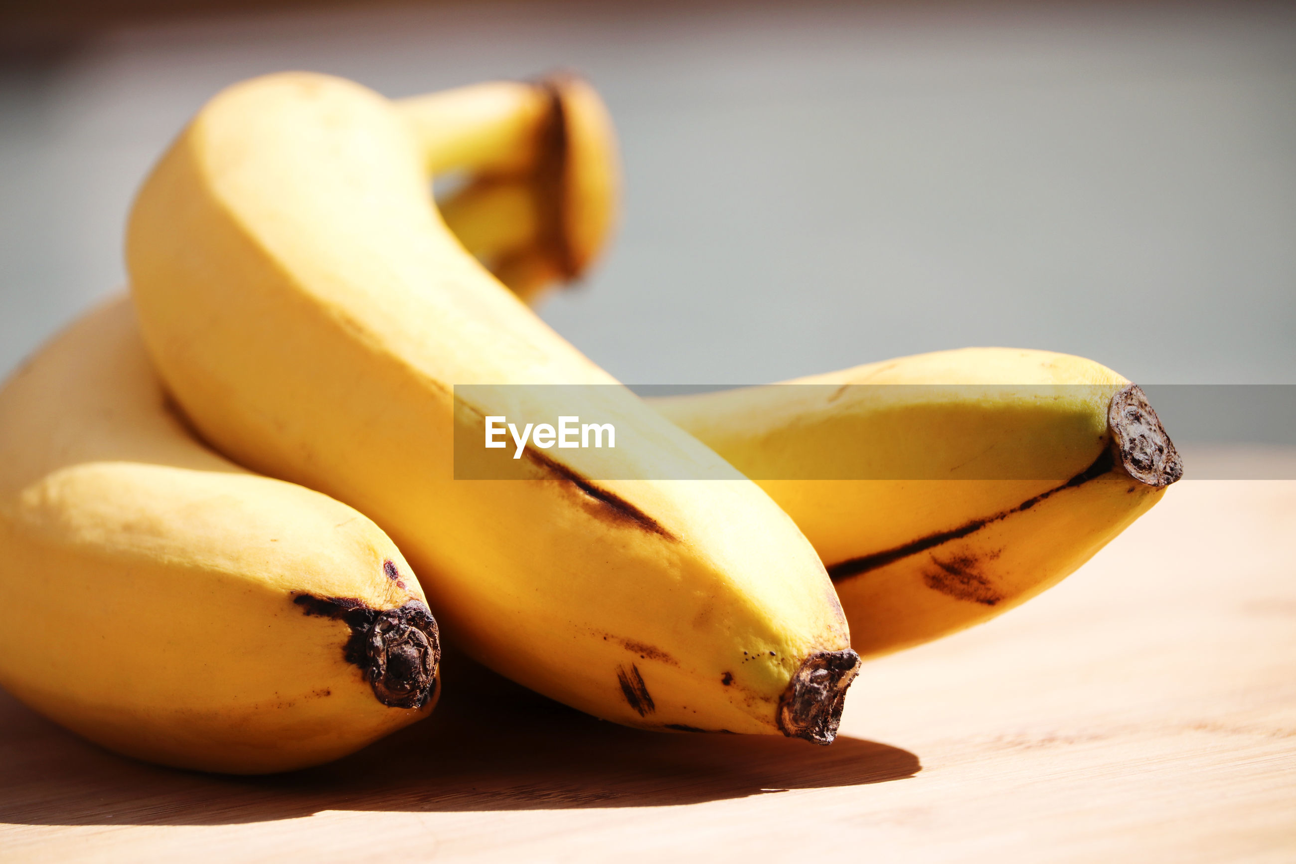 CLOSE-UP OF YELLOW BANANAS ON TABLE