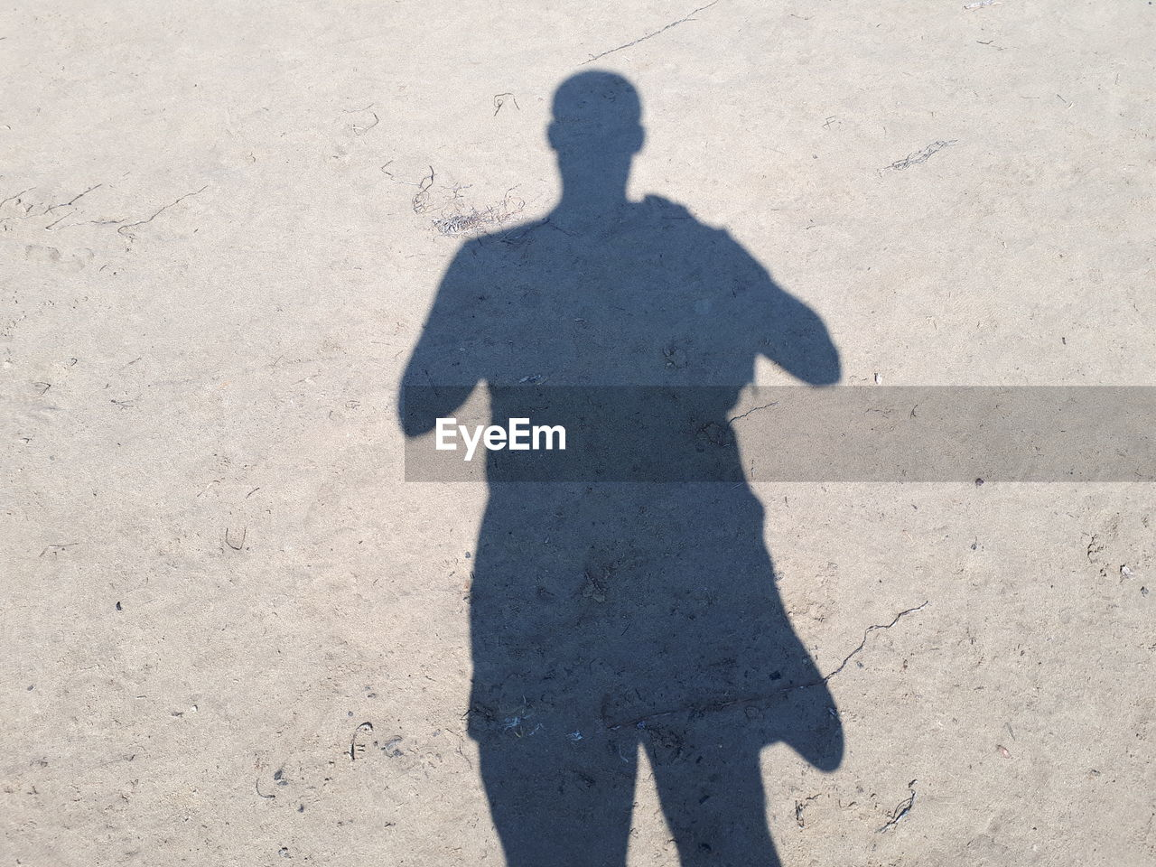 shadow, sunlight, nature, focus on shadow, day, one person, high angle view, real people, land, sand, standing, lifestyles, outdoors, sunny, leisure activity, men, unrecognizable person, field, dirt