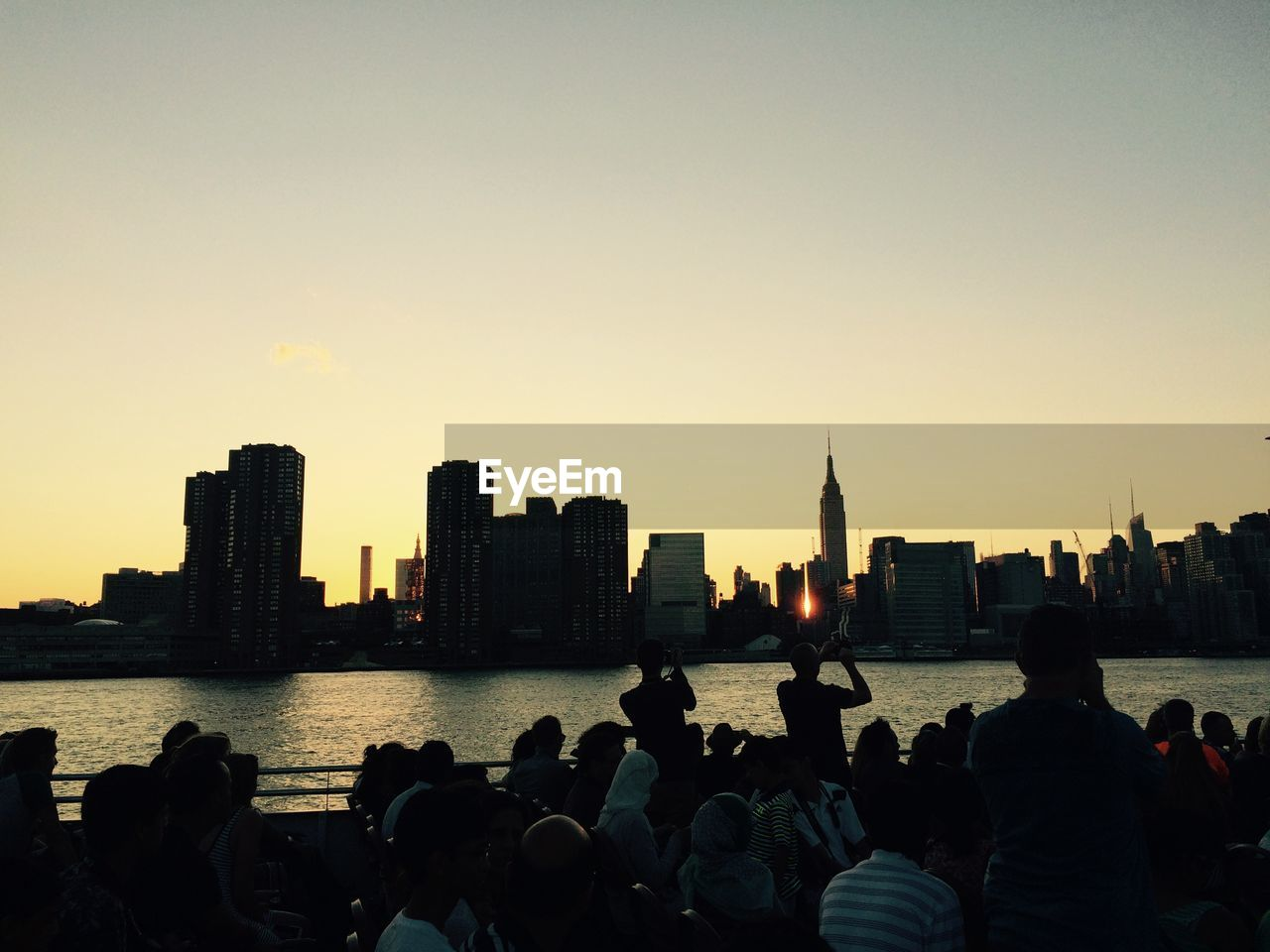 Crowd by river against clear sky in city at dusk