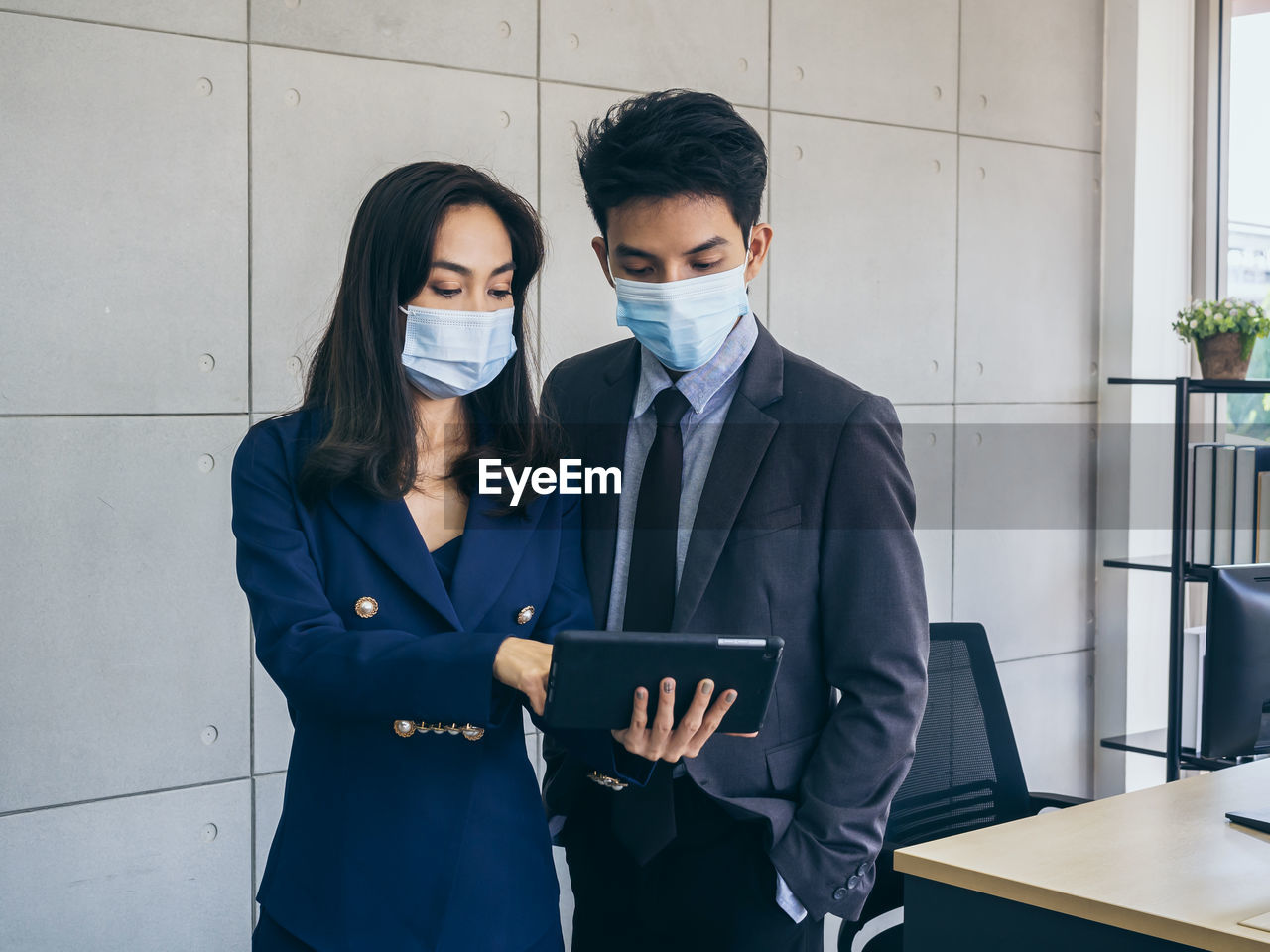 View of business people wearing flu mask brainstorming while using digital tablet at office