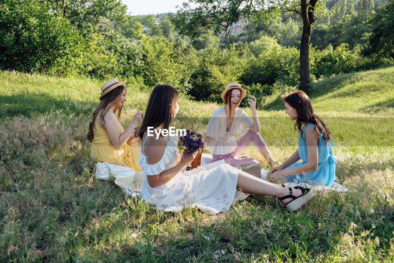 FRIENDS SITTING ON FIELD BY TREE