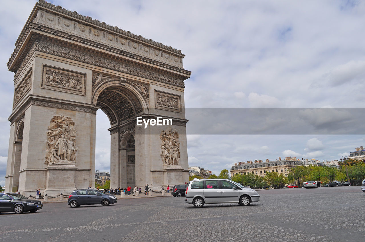car, architecture, triumphal arch, built structure, cloud - sky, mode of transport, arch, land vehicle, transportation, sky, history, city, travel destinations, outdoors, day, building exterior, road, no people