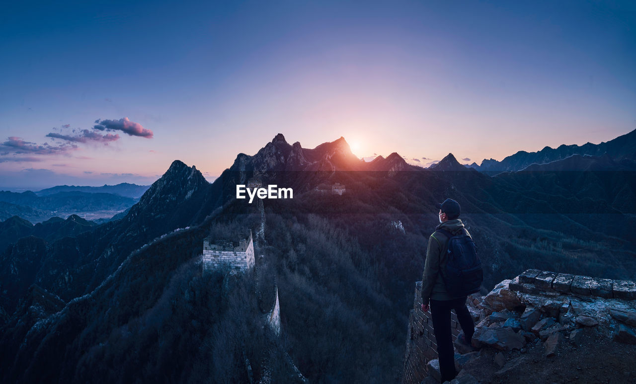 Man With Backpack Looking At View While Standing On Cliff Against Mountain And Sky During Sunset