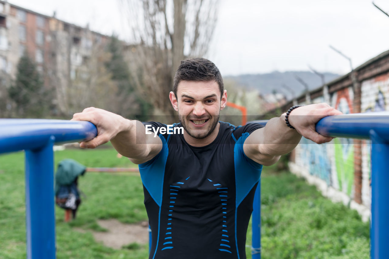 Portrait of young man exercising at park