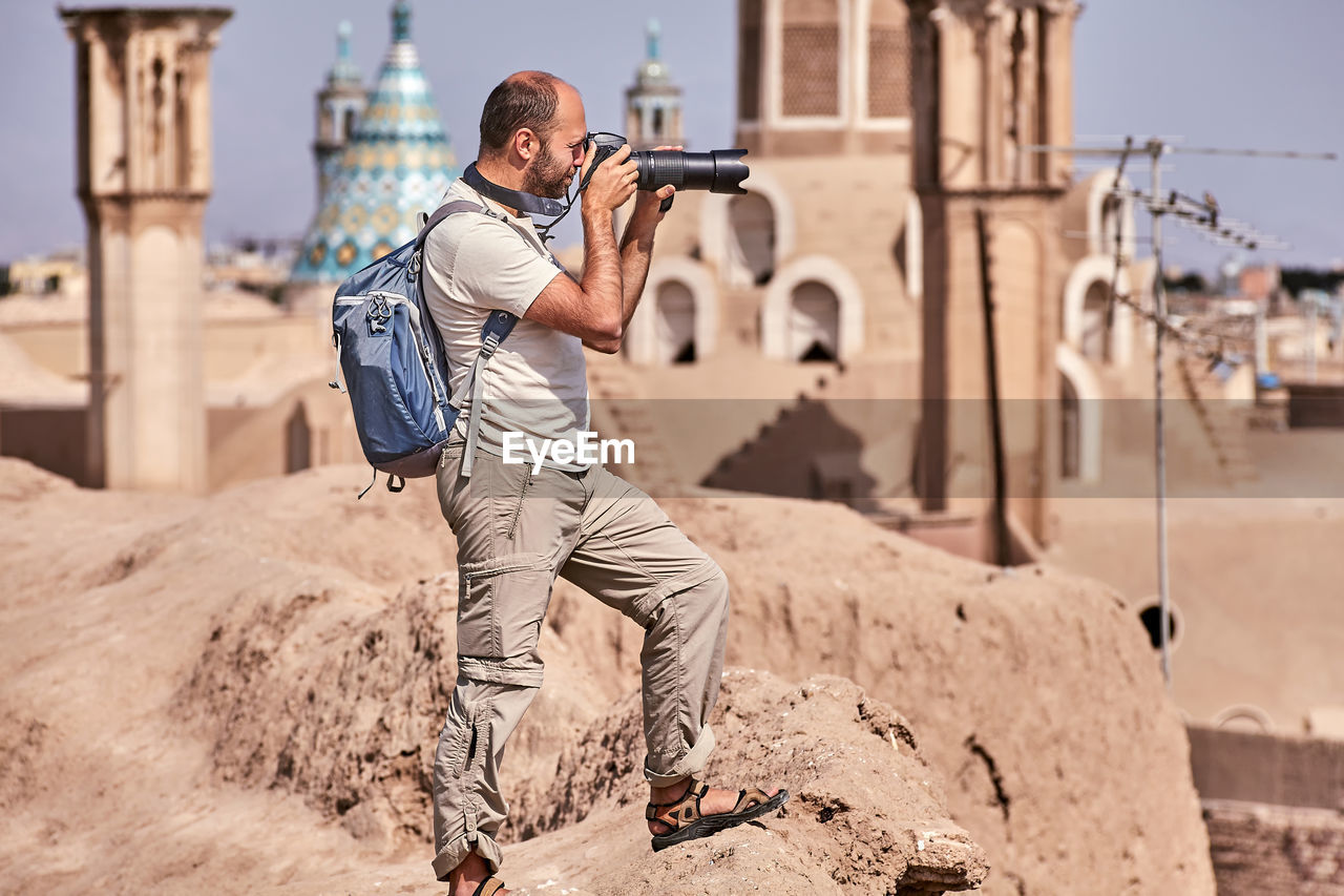 real people, men, technology, casual clothing, lifestyles, architecture, one person, focus on foreground, holding, young men, nature, building exterior, photography themes, males, built structure, day, camera - photographic equipment, young adult, standing, outdoors, photographer