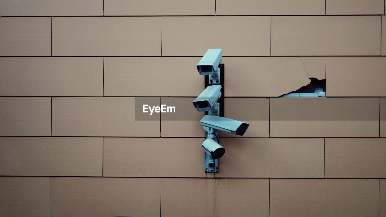 Full frame shot of surveillance camera on tiled wall