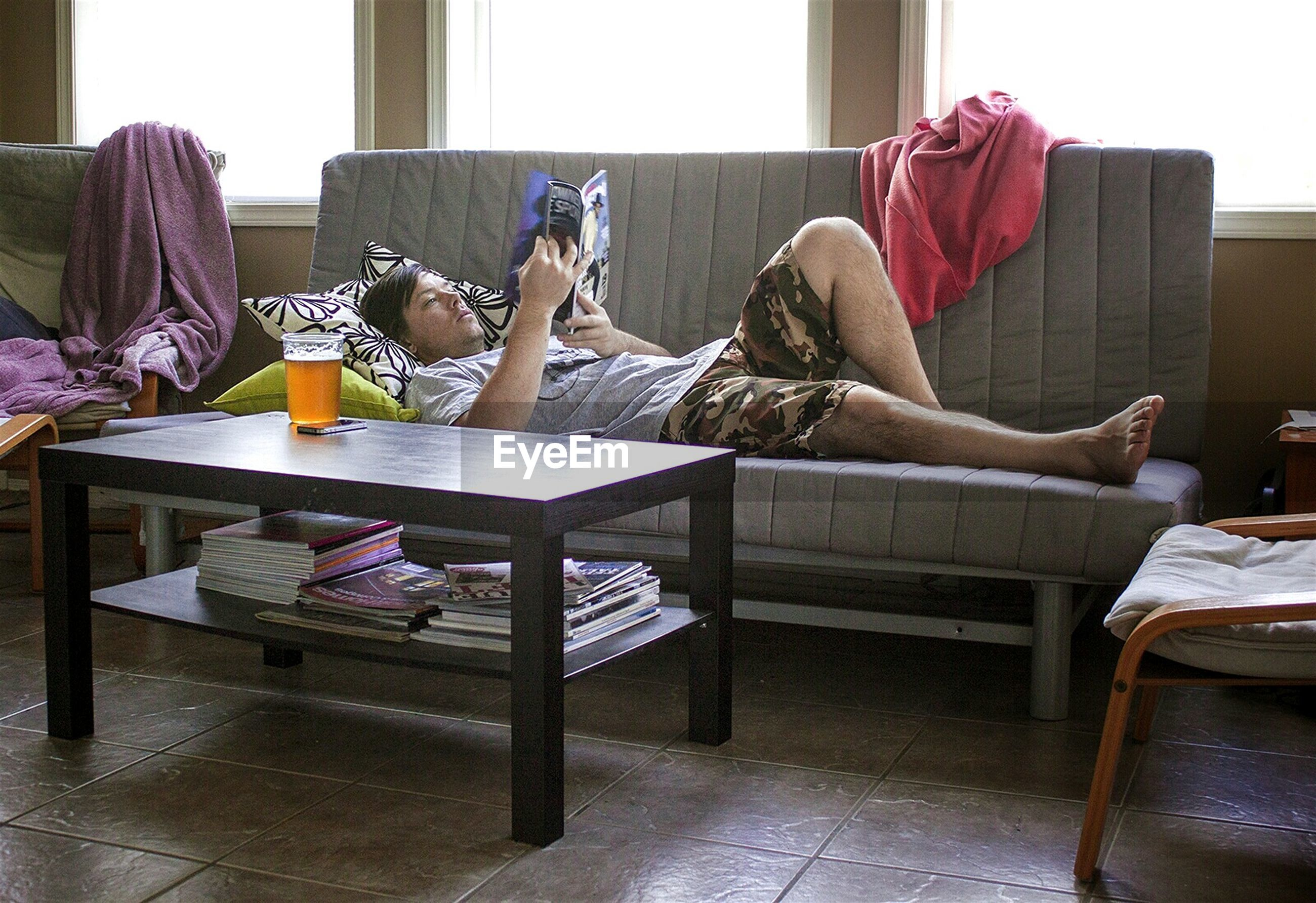 Full length of man reading book while resting on sofa at home