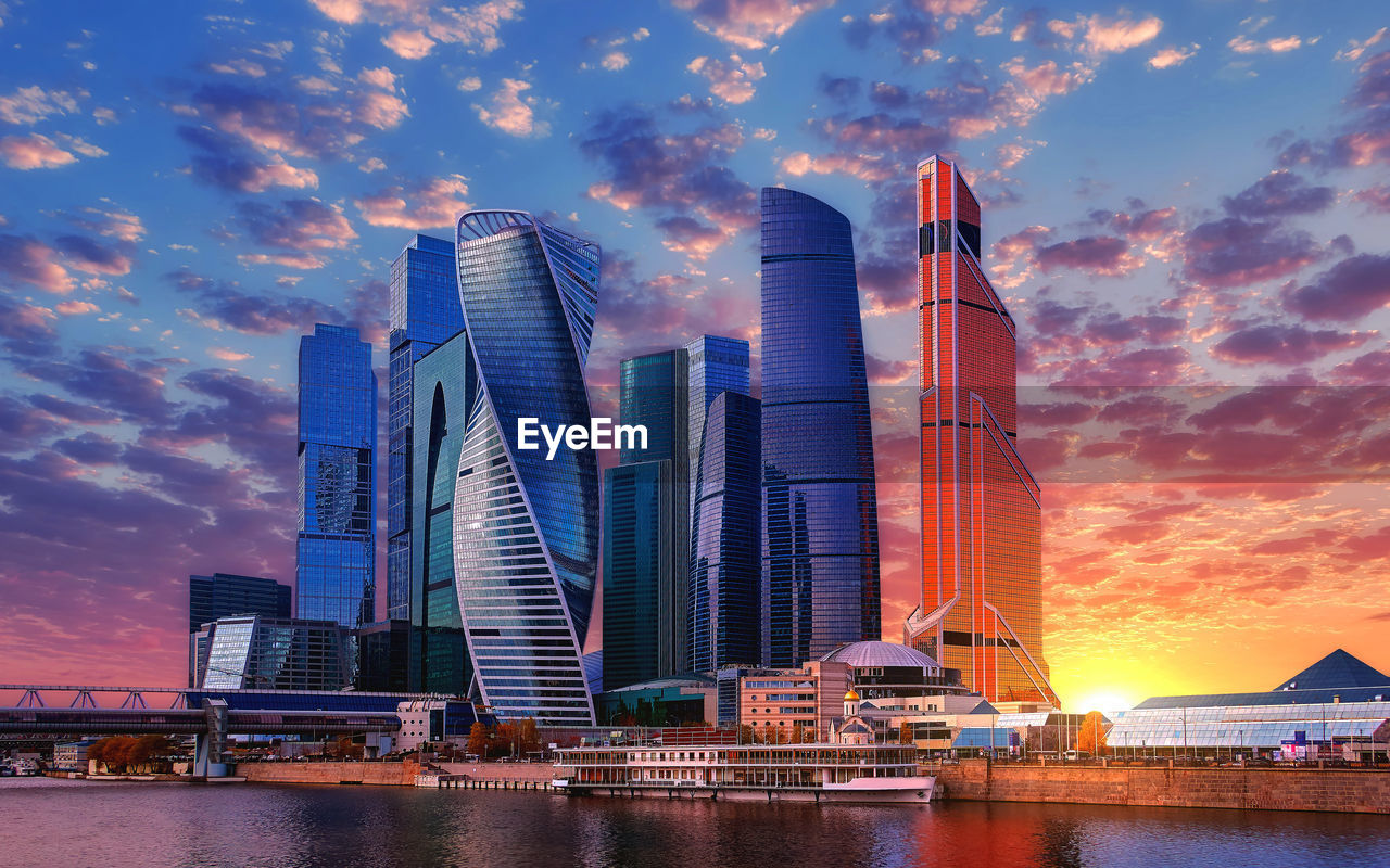 built structure, architecture, building exterior, sky, water, cloud - sky, building, city, office building exterior, sunset, modern, tall - high, waterfront, skyscraper, nature, office, no people, river, urban skyline, outdoors, cityscape, financial district
