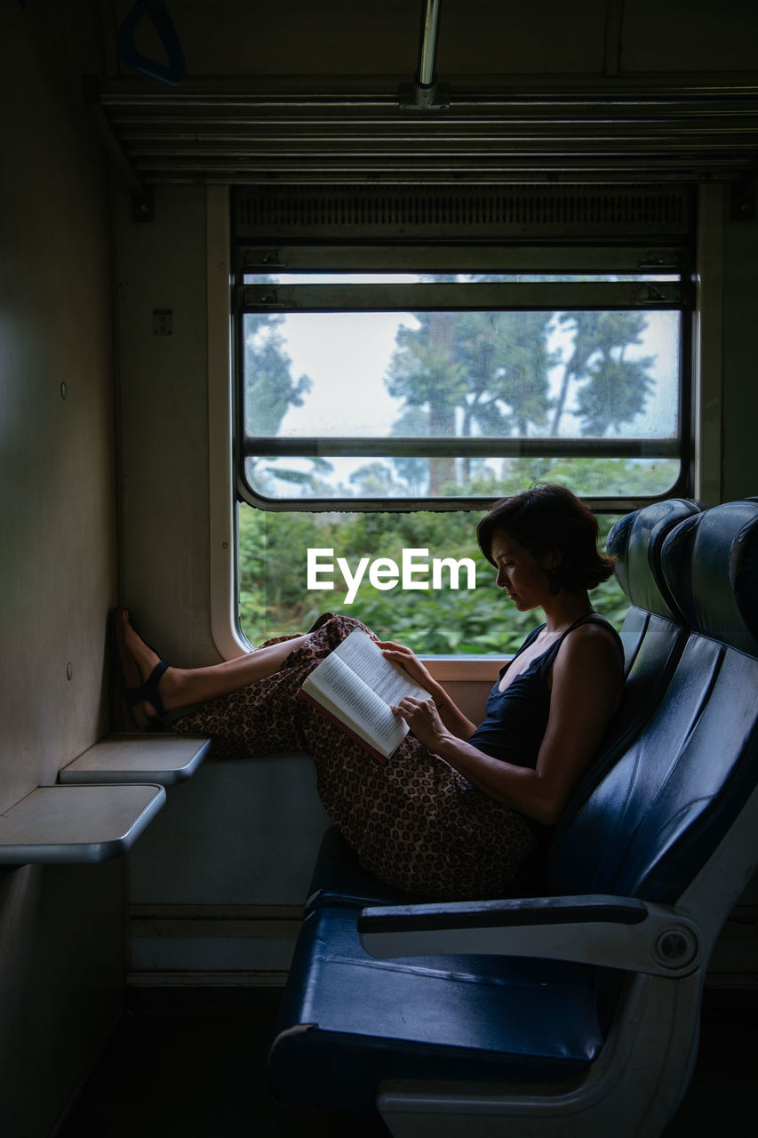 one person, real people, window, indoors, sitting, lifestyles, seat, leisure activity, day, vehicle interior, adult, vehicle seat, casual clothing, chair, full length, relaxation, train, public transportation, side view