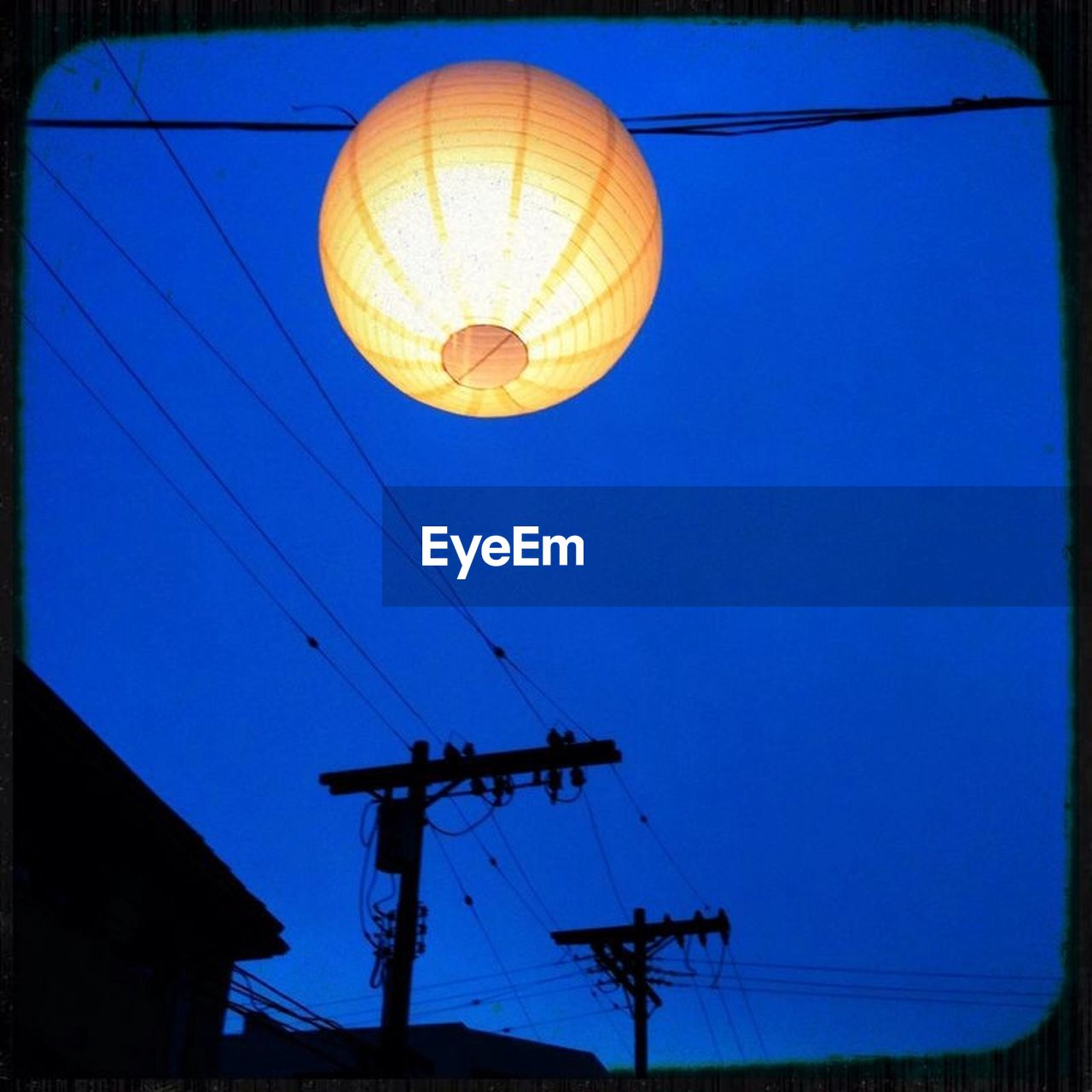 low angle view, hanging, blue, clear sky, lantern, night, electricity, illuminated, outdoors, flying, sky, no people, hot air balloon