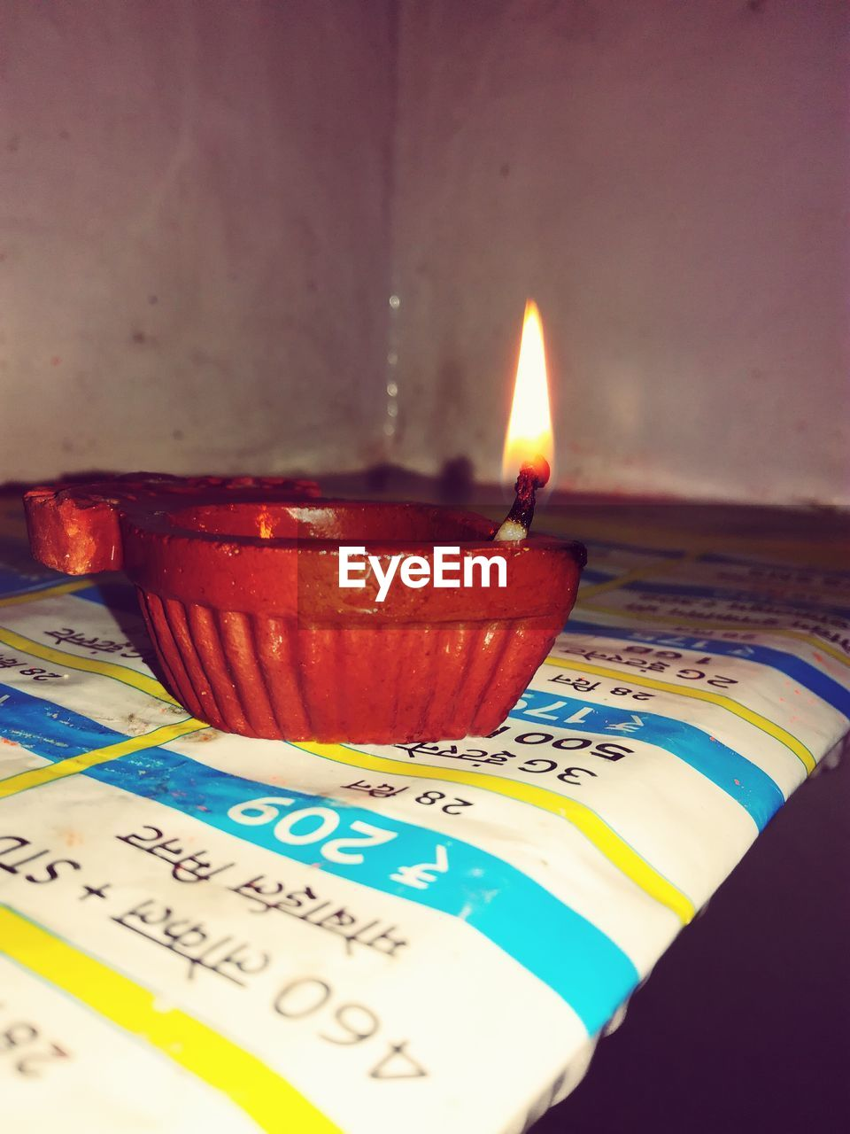 flame, candle, burning, heat - temperature, text, no people, indoors, table, close-up, illuminated, diya - oil lamp, multi colored, oil lamp, night
