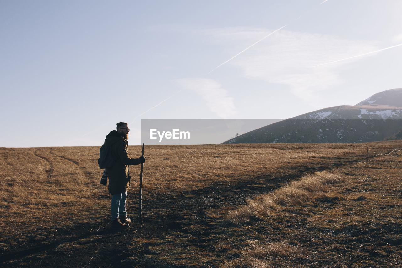 Side view  of man on landscape against sky