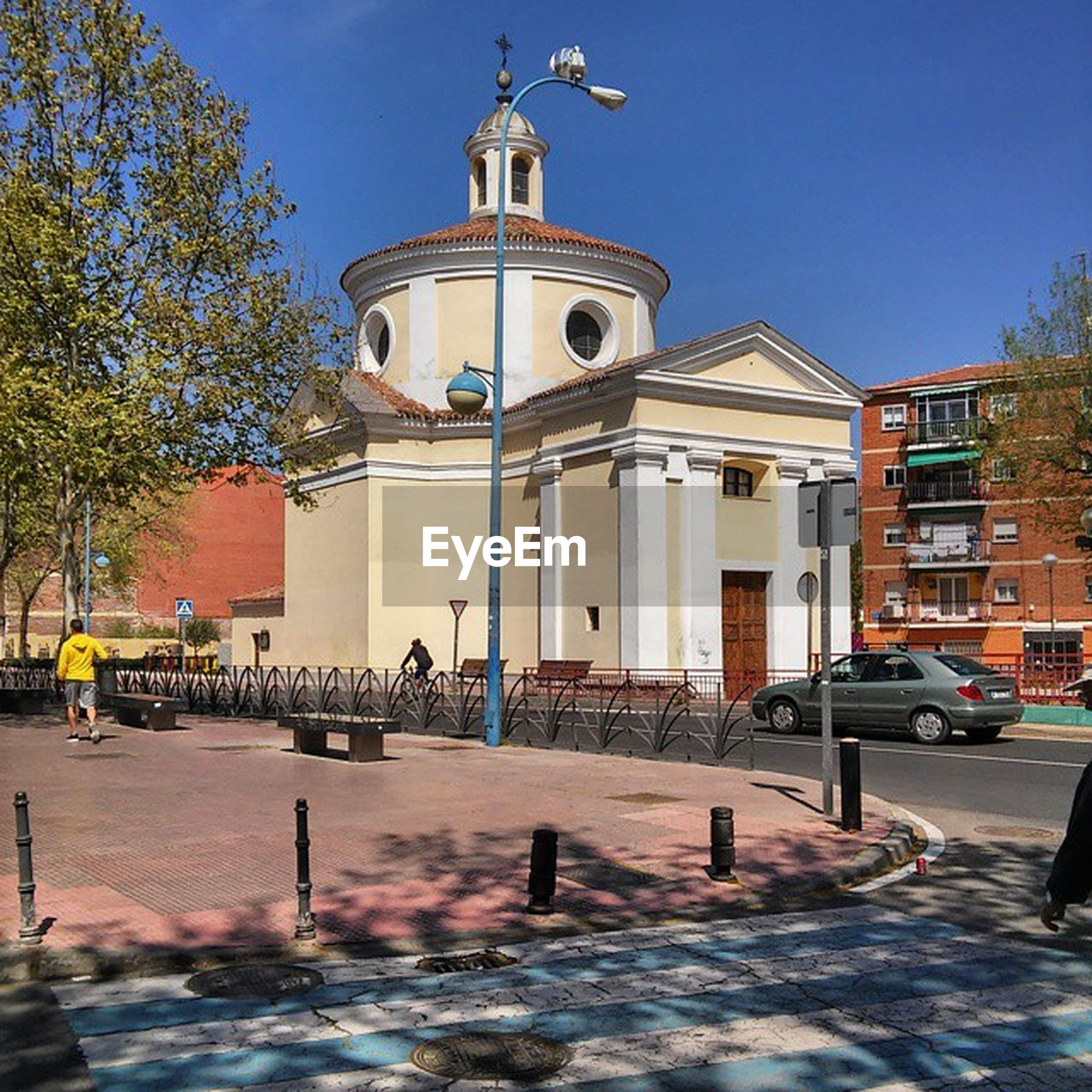 building exterior, architecture, built structure, clear sky, church, place of worship, religion, spirituality, tree, street, incidental people, transportation, dome, sunlight, car, blue, road, facade