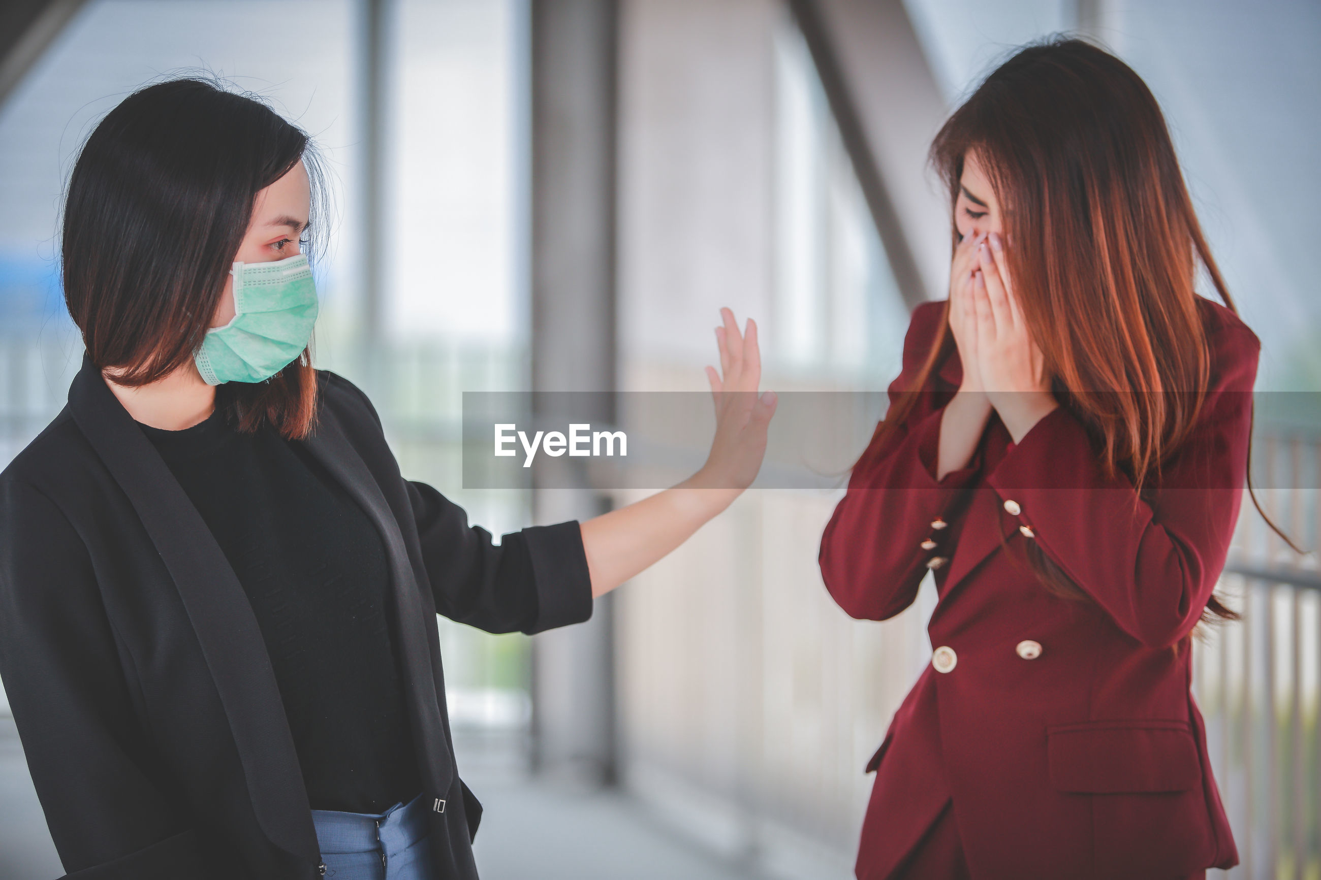 Woman showing stop gesture to female colleague sneezing
