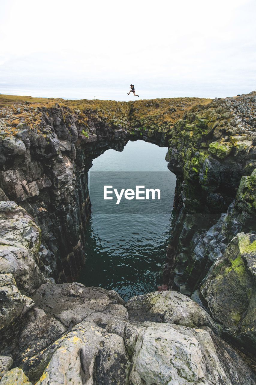 Scenic View Of Man Jumping On Cliff