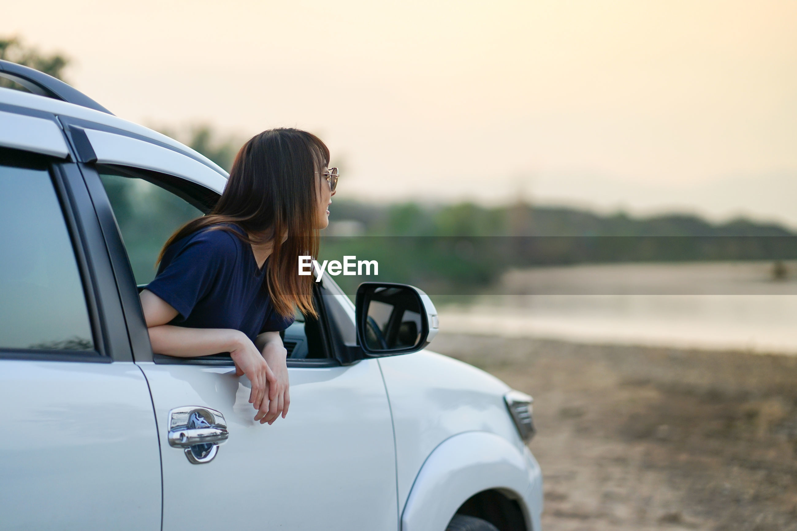 Woman peeking through car window against sky