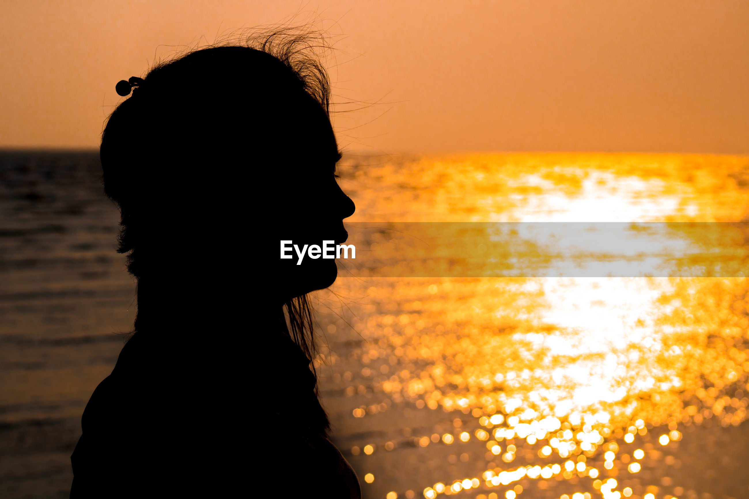 Silhouette woman against sea during sunset