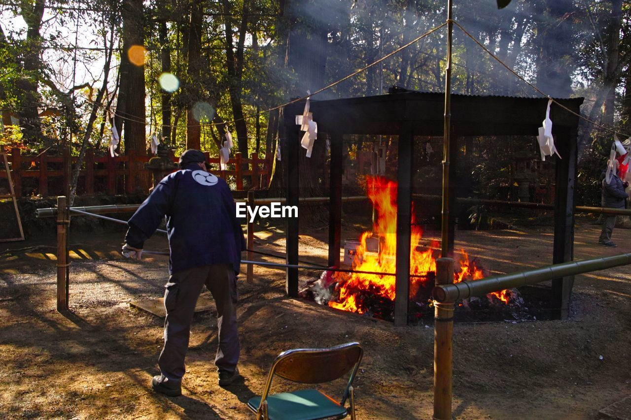 heat - temperature, real people, burning, fire, men, flame, fire - natural phenomenon, tree, nature, standing, one person, plant, lifestyles, leisure activity, wood - material, rear view, day, full length, motion, outdoors, preparing food, bonfire