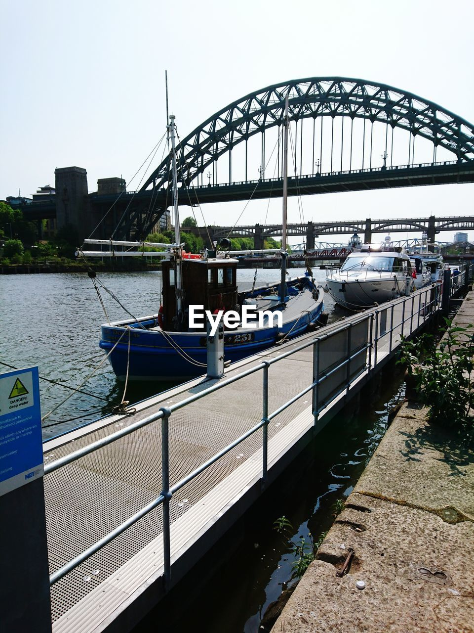 Boats moored in river against tyne bridge