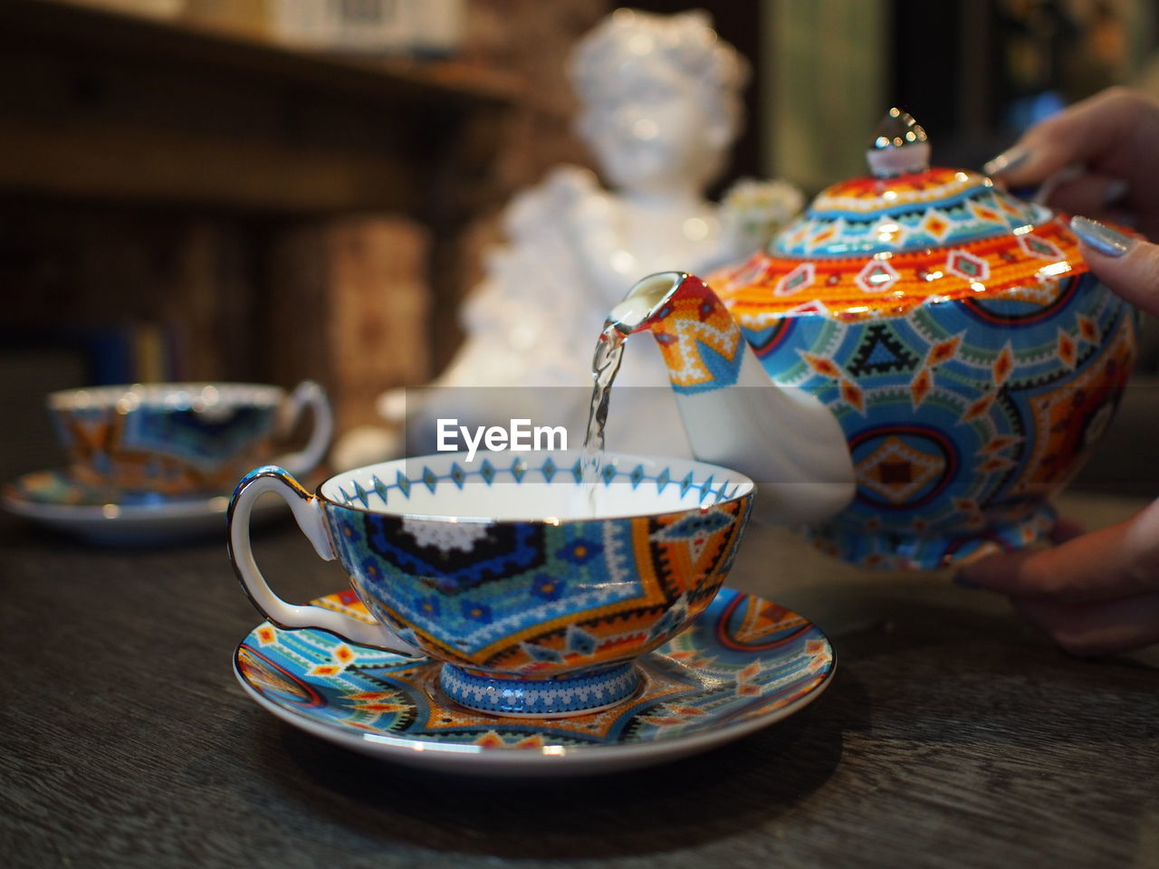 table, food and drink, drink, indoors, cup, real people, one person, focus on foreground, pattern, mug, tea, hot drink, refreshment, kitchen utensil, crockery, hand, human hand, close-up, tea cup, saucer, teapot, floral pattern