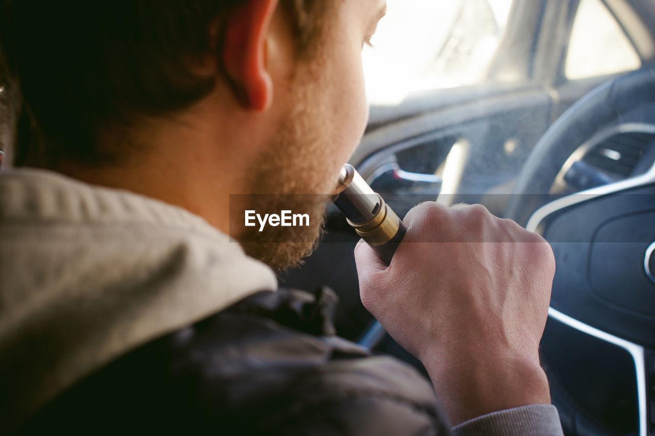 Man Smoking Electronic Cigarette In Car