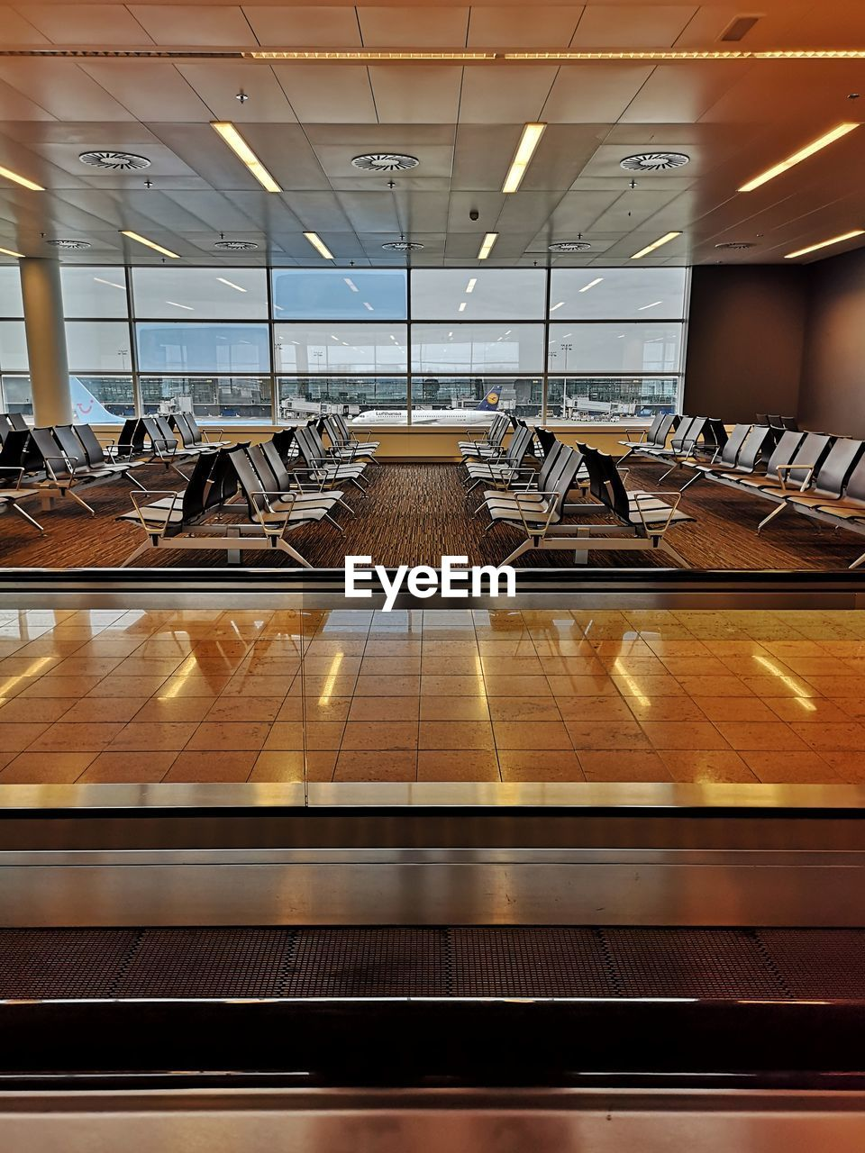 indoors, absence, seat, no people, window, airport, flooring, empty, architecture, reflection, illuminated, ceiling, day, glass - material, modern, airport departure area, chair, built structure, tile, tiled floor, airport terminal