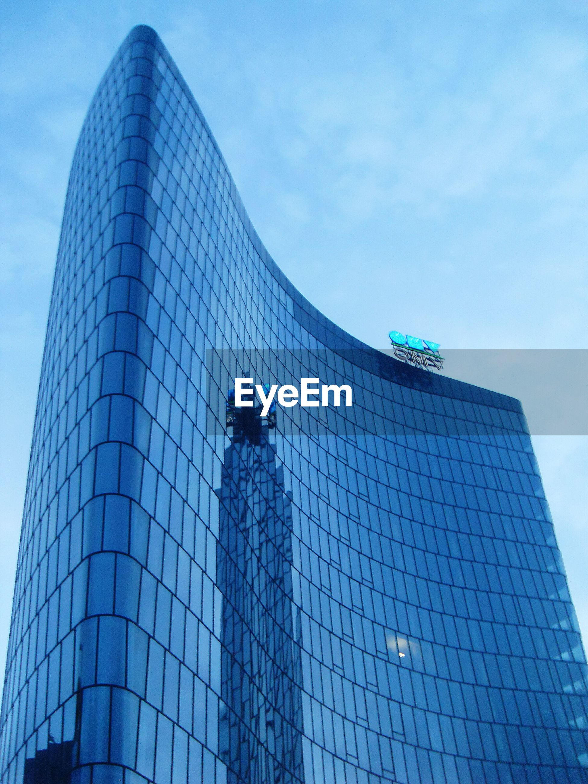 building exterior, low angle view, architecture, built structure, modern, skyscraper, office building, tall - high, city, tower, sky, blue, glass - material, building, capital cities, day, reflection, outdoors, tall, famous place