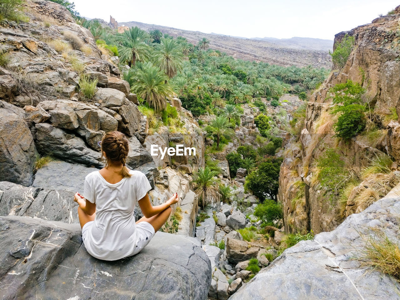 Rear View Of Woman Sitting On Rock By Mountains