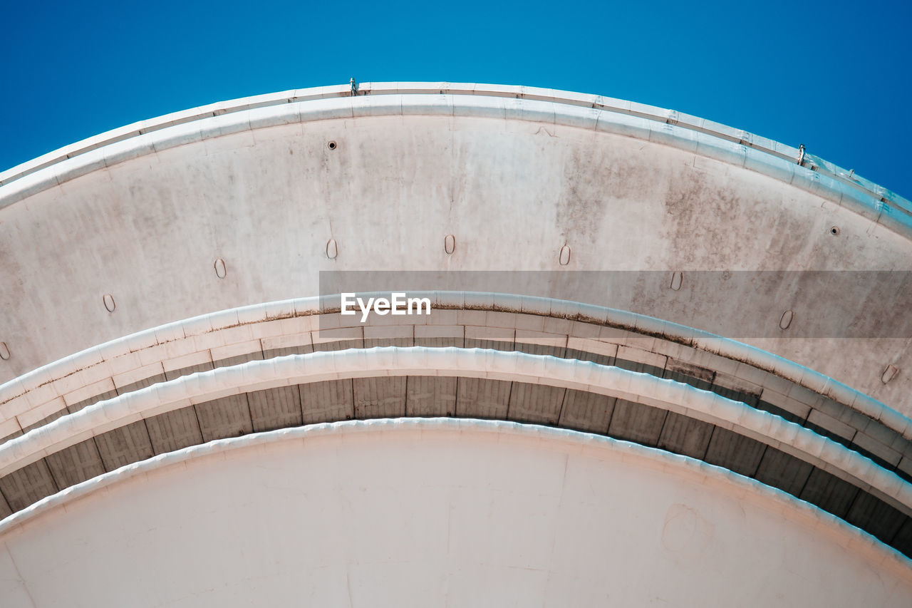 Low angle view of storage tank against blue sky