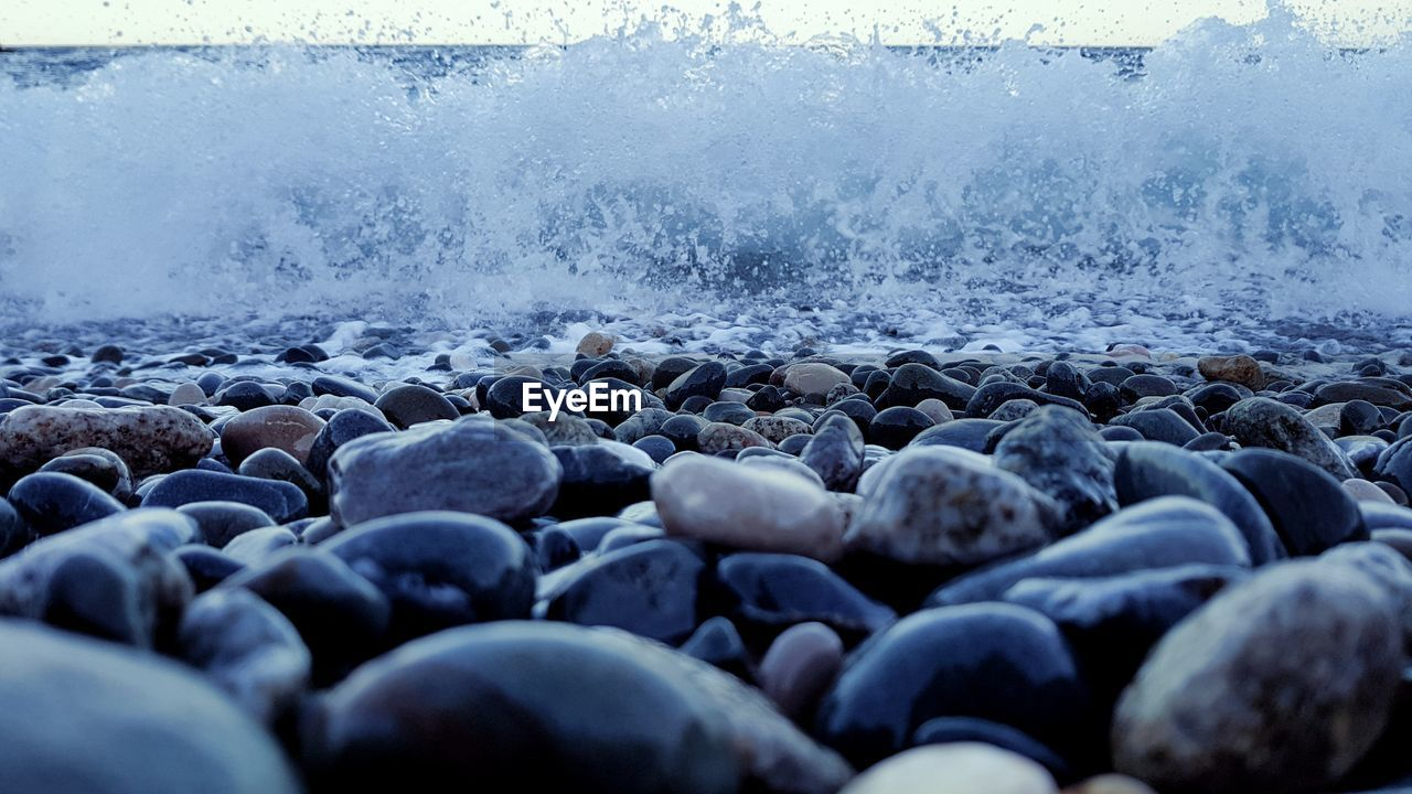 pebble, pebble beach, shore, surface level, beach, sea, no people, water, wave, nature, motion, day, outdoors, beauty in nature, close-up
