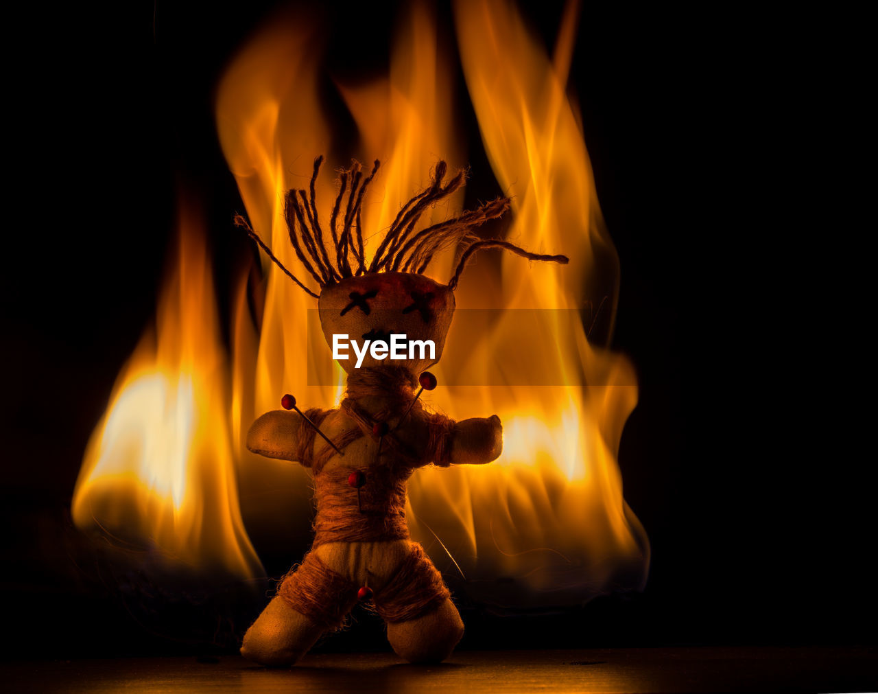 Close-up of voodoo doll and fire against black background