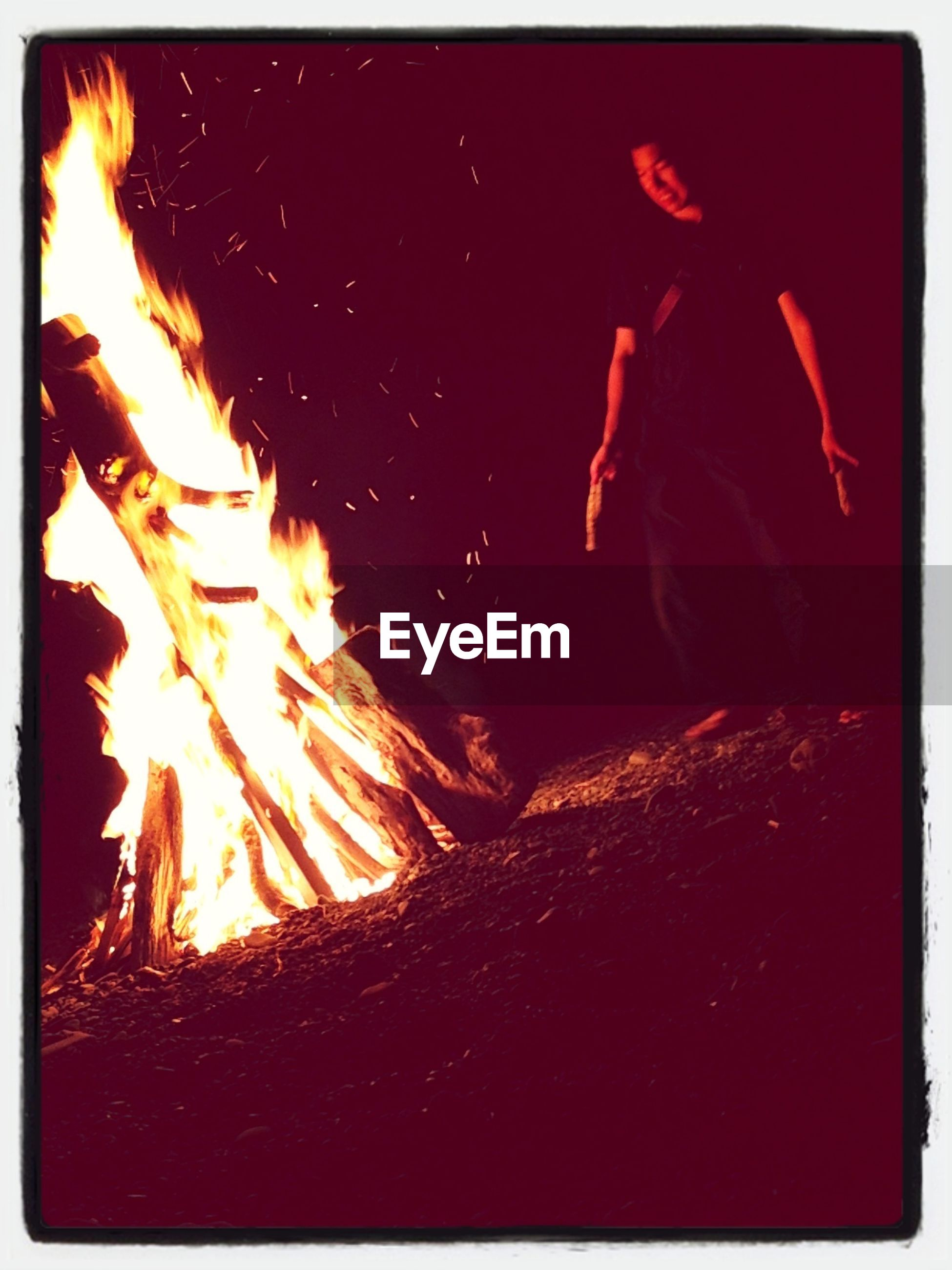 transfer print, auto post production filter, lifestyles, leisure activity, night, men, motion, full length, silhouette, outdoors, enjoyment, unrecognizable person, water, standing, togetherness, orange color, bonfire