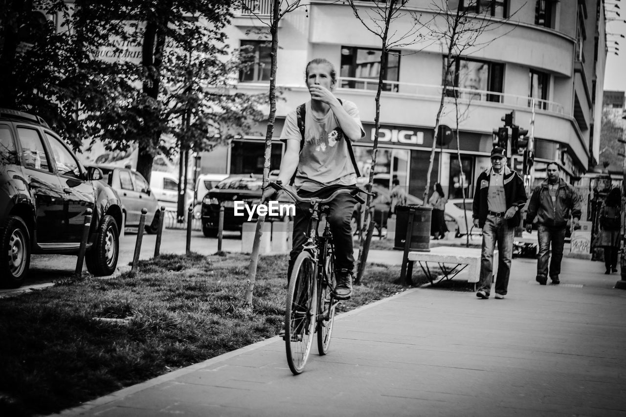 bicycle, transportation, cycling, mode of transport, riding, land vehicle, street, real people, architecture, outdoors, road, built structure, building exterior, tree, city, one person, day, biker, people