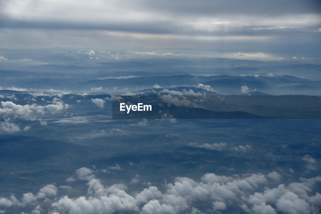 Aerial View Of Landscape During Foggy Weather Seen From Airplane Window