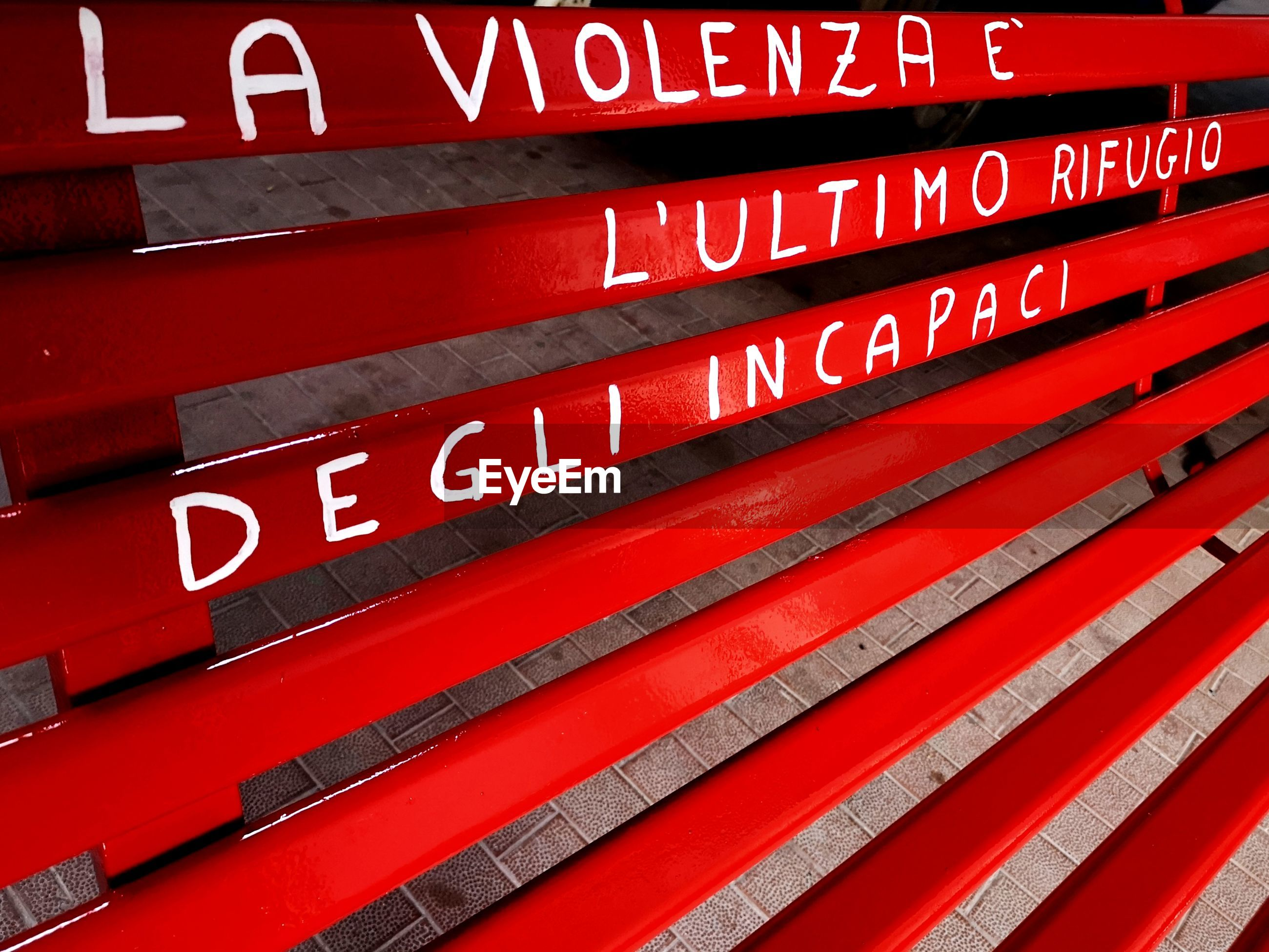 LOW ANGLE VIEW OF TEXT ON RED WALL