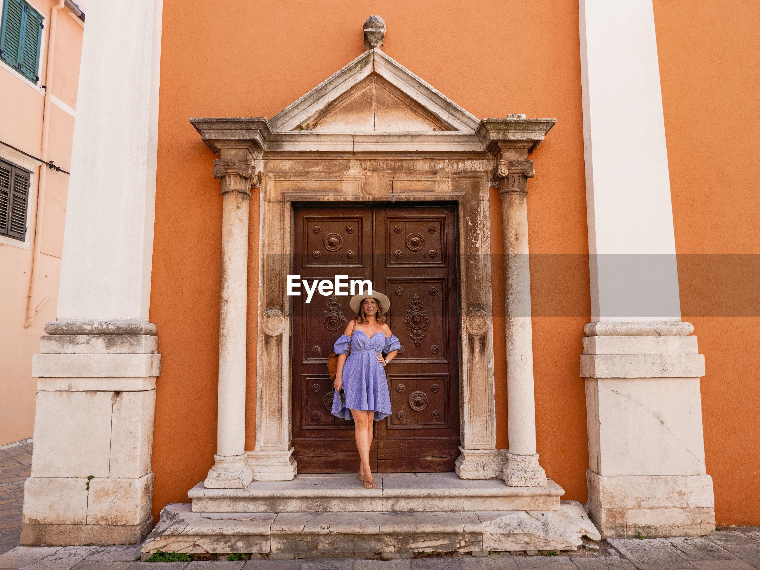 Portrait of woman standing against door of building