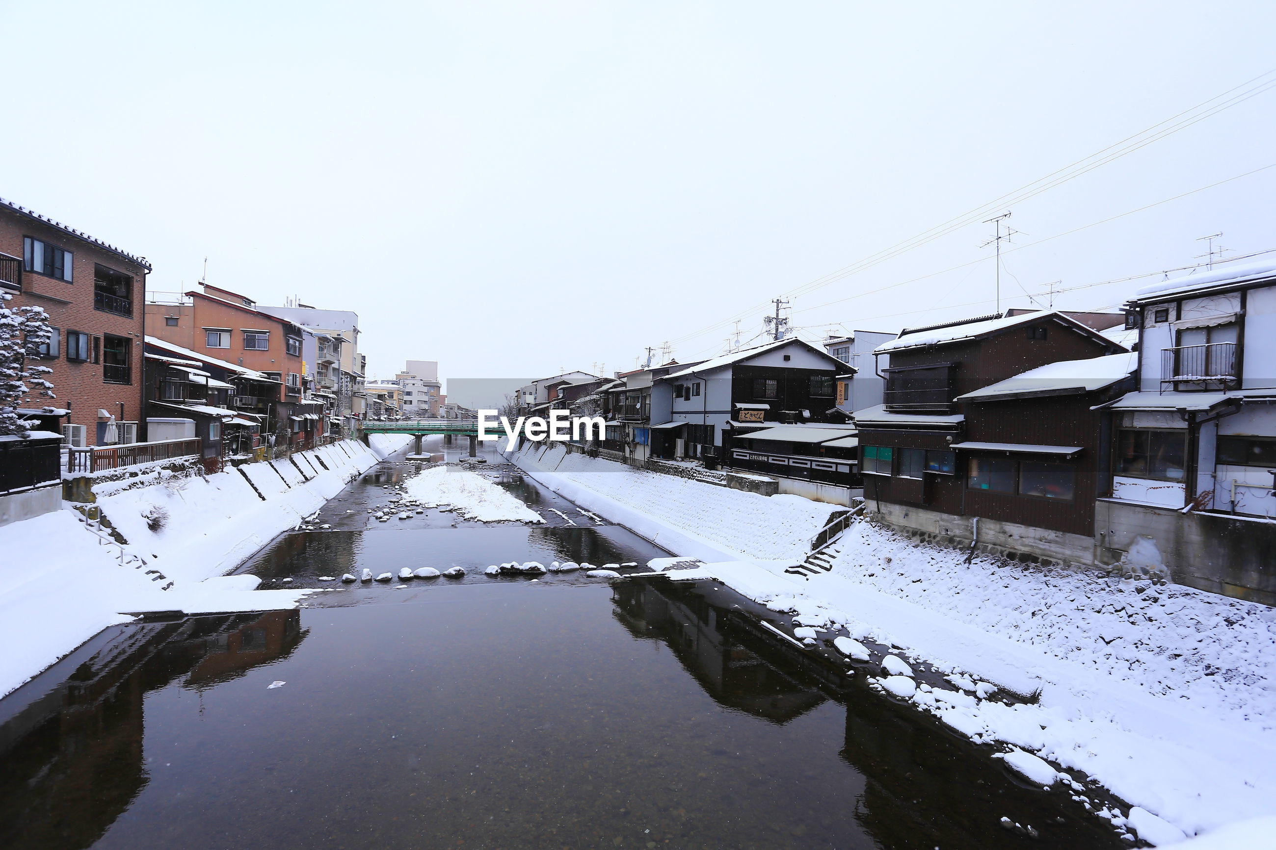 SNOW COVERED BUILDINGS BY CANAL AGAINST SKY