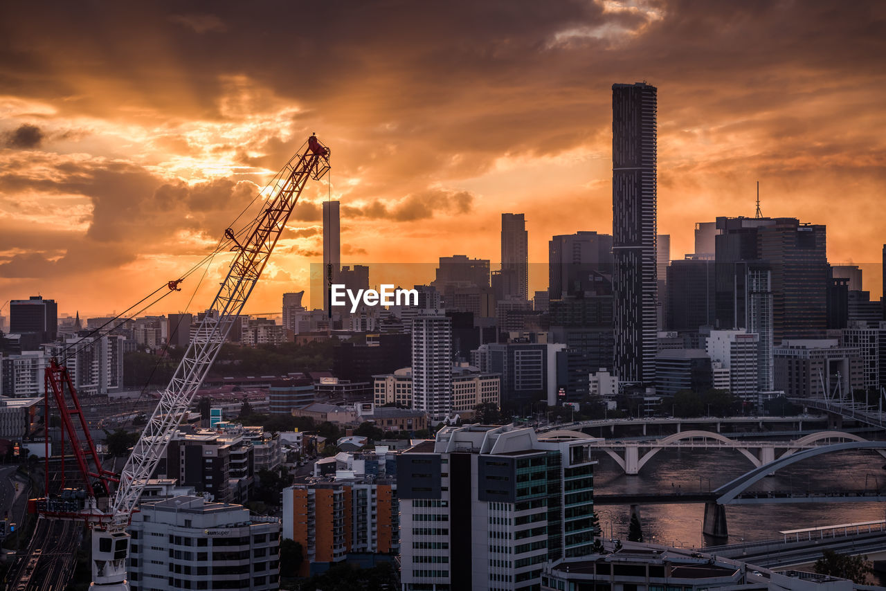 sky, architecture, building exterior, built structure, sunset, cloud - sky, city, building, machinery, crane - construction machinery, no people, cityscape, tall - high, office building exterior, nature, orange color, construction industry, outdoors, industry, skyscraper, development, modern