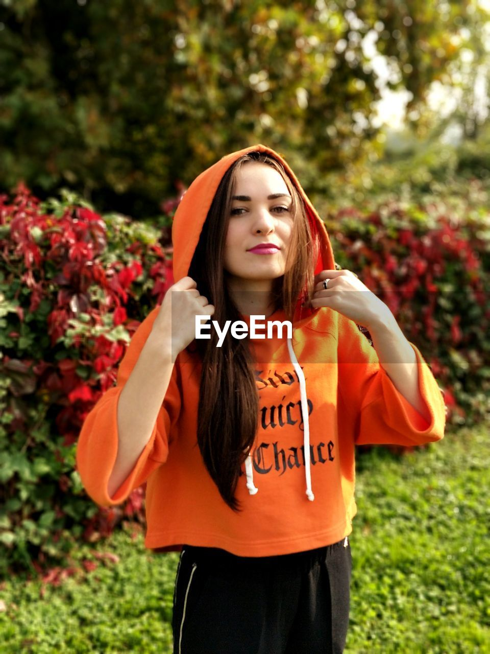 Portrait Of Young Woman In Orange Hooded Shirt Standing Against Trees