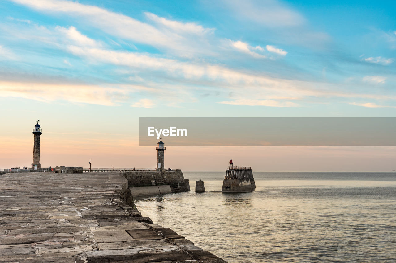 sky, sea, water, cloud - sky, sunset, architecture, built structure, tower, beauty in nature, scenics - nature, nature, building exterior, guidance, no people, orange color, lighthouse, protection, building, security, horizon over water, outdoors