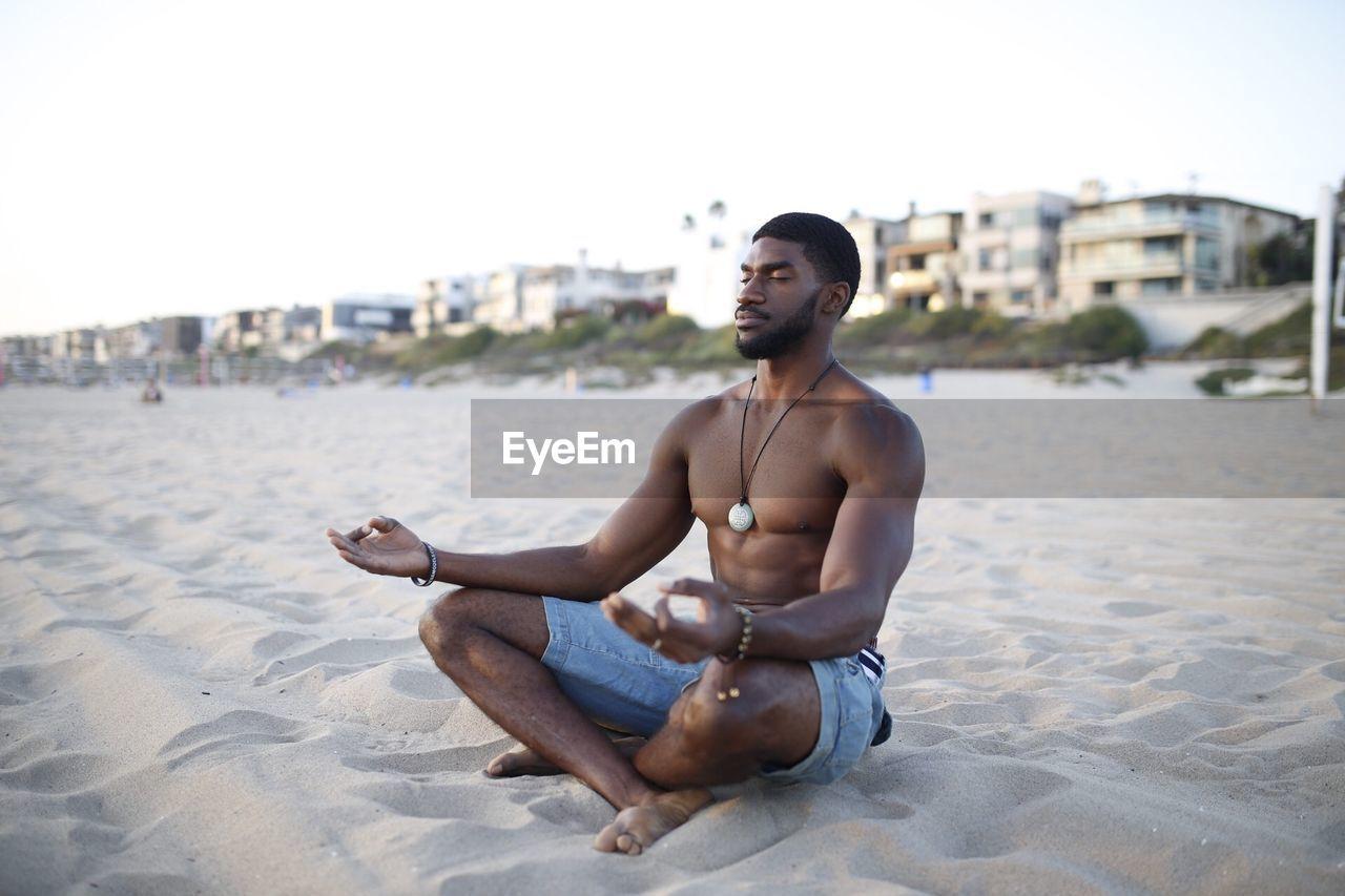 Shirtless Muscular Man Meditating At Beach Against Clear Sky